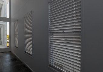 Three venetian blinds down hallway
