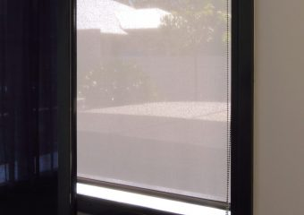 Sun control roller blind behind TV