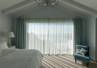 Patterned S fold sheers over blockout curtains under pitched roof-open
