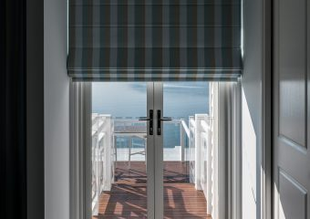 Patterned blockout roman blinds over french doors-half closed
